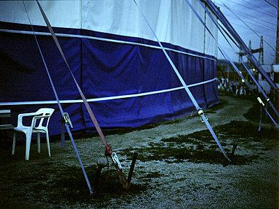 Zirkuszelt im Anschnitt mit Spannseilen und Gartenstuhl im Halbdunkel - p627m1035887 von Anja Gödicke