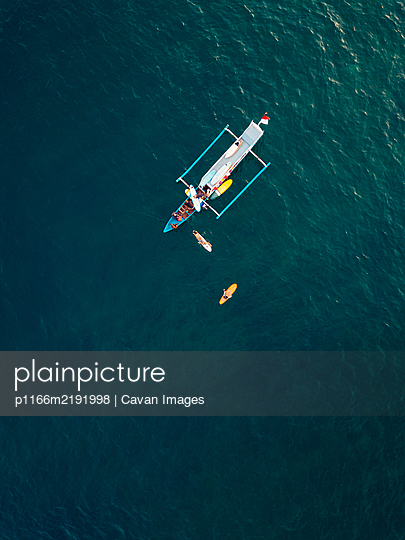 Aerial view of surfers and boat in the ocean, Lombok, Indonesia - p1166m2191998 by Cavan Images