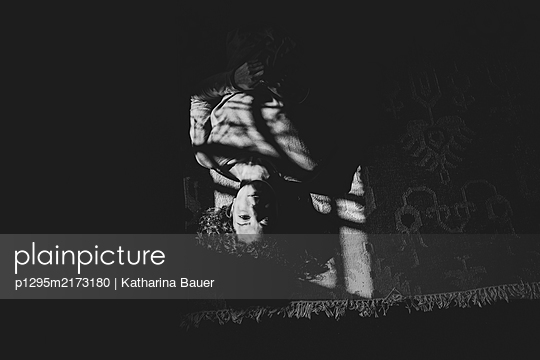 Woman in selfquaratine lying on carpet - p1295m2173180 by Katharina Bauer