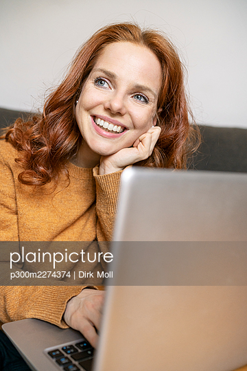 Beautiful smiling redhead woman thinking while looking away at home - p300m2274374 by Dirk Moll