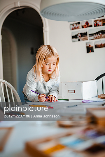 Girl at home doing homework - p312m2237186 by Anna Johnsson