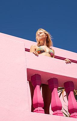 Mondäne Frau auf pinkem Balkon - p045m1223734 von Jasmin Sander