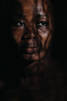 close-up of black woman with shadows of light  - p1540m2110360 by Marie Tercafs
