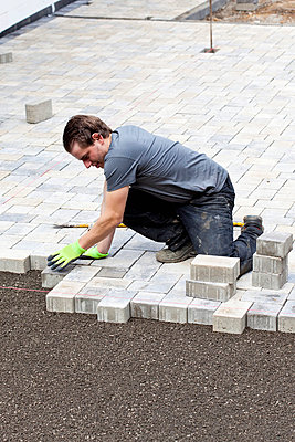 Young man assembling paving stones - p300m798166f by Dieter Heinemann