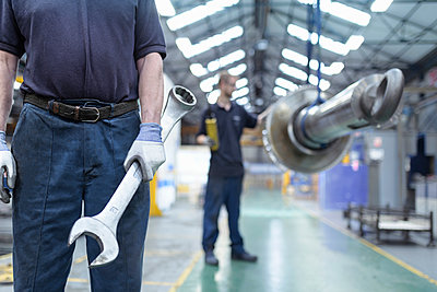 Close up of engineer holding large spanner in gearbox factory - p429m2019155 by Monty Rakusen