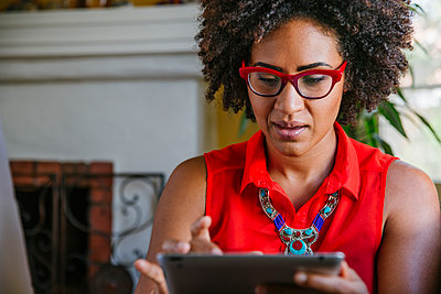 Mixed race woman using digital tablet - p555m1408381 by Shestock