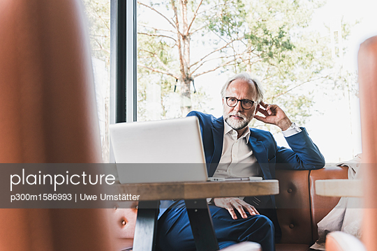 Mature businessman sitting at table in a cafe using laptop - p300m1586993 von Uwe Umstätter