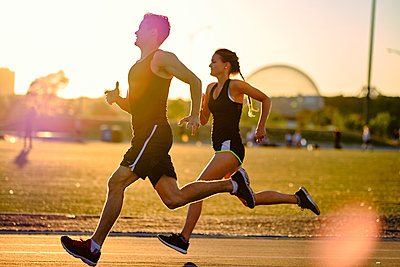 Sprinters racing around track during workout with sunset behind, Montreal, Quebec, Canada - p1362m2024408 by Charles Knox