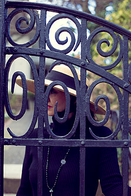 Woman with hat behind a gate - p1621m2254235 by Anke Doerschlen