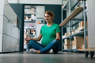 Smiling pregnant woman sitting on floor in office having a yoga break - p300m2080779 by Kniel Synnatzschke