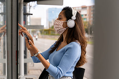 Woman in face mask wearing headphones while purchasing bus ticket during COVID-19 - p300m2225062 by VITTA GALLERY