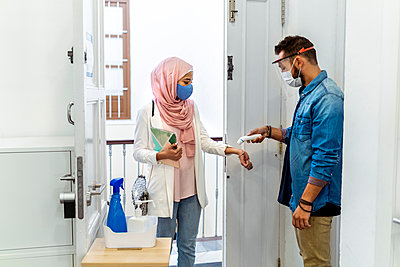 Man checking temperature of woman while standing at office entrance - p300m2226978 by Manu Padilla Photo