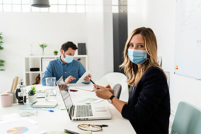 Business people wearing protective masks working in office  - p300m2242553 by Giorgio Fochesato