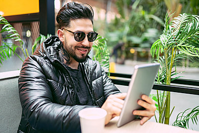 Smiling hipster man using digital tablet at table in sidewalk cafe - p300m2252100 by Jose Carlos Ichiro