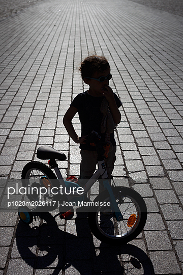 Young boy and his bike - p1028m2026117 von Jean Marmeisse