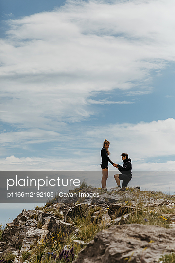 happy boyfriend puts a ring on his girlfriend's hand after proposal - p1166m2192105 by Cavan Images
