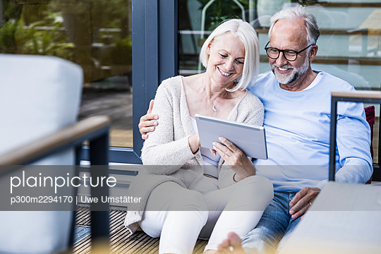 Smiling woman using digital tablet while sitting by man at balcony - p300m2294170 by Uwe Umstätter