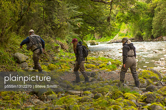 Caucasian friends walking in remote river - p555m1312270 by Steve Smith
