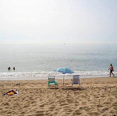 Ein Sonnenschirm und zwei Stühle am Strand, Malaga - p1082m2289275 von Daniel Allan