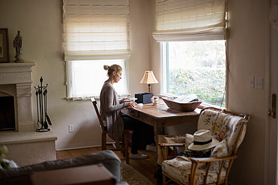 Blond woman sitting at a desk by a window, looking at photographs. - p1100m1080236 by Mint Images