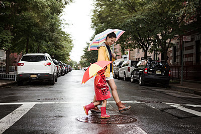 Side view of mother and daughter holding umbrellas while crossing road - p1166m1096324f by Cavan Images