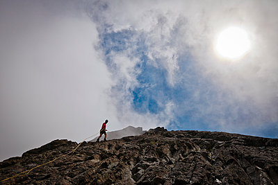 Low angle view of hiker climbing rock formations against cloudy sky - p1166m1531497 by Cavan Images