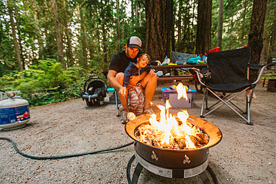 Dad and son roasting marshmallows over propane fire at campsite - p1166m2111629 by Cavan Images