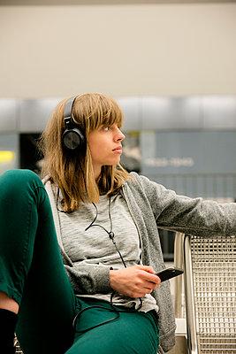 Junge Frau mit Kopfhörer und Handy in der U-Bahnstation - p1212m1136996 von harry + lidy