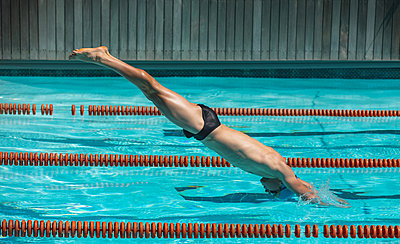 Young male swimmer jumping into water of a swimming pool - p1315m2091013 by Wavebreak