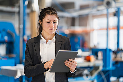 Businesswoman using digital tablet while standing at industry - p300m2250796 by Daniel Ingold