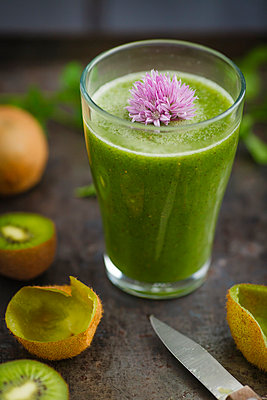 Glass of smoothie with kiwi, parsley and blooming chives, close up - p300m827136f by Elisabeth Cölfen