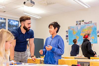 Teacher with schoolboy in classroom - p312m2174813 by Scandinav