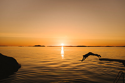 Silhouette of woman jumping into sea - p312m2216972 by Stina Gränfors