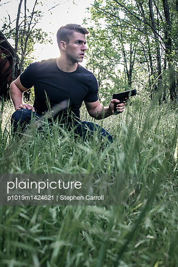 Armed man on the alert in the meadow - p1019m1424621 by Stephen Carroll