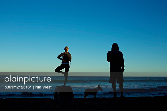 Silhouette young couple with dog practicing yoga on sunrise beach - p301m2123161 by Nik West