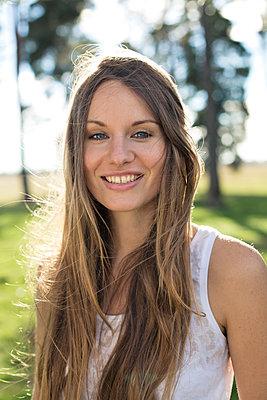 Portrait of smiling young woman in nature - p300m2081324 von Philipp Nemenz
