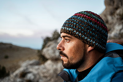 Thoughtful man hiking on mountain during vacation - p300m2241086 by Rafa Cortés