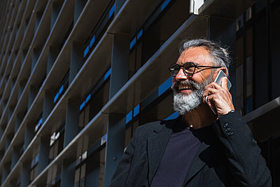 Barcelona, Spain. Senior businessman with long grey hair and glasses in the city. Business, hair style, mature, senior, young businessman, caucasian, entrepreneur, handsome, grey hair, bearded, 50-60 years, job, technology, computer, bar, connection, talk - p300m2276290 von NOVELLIMAGE