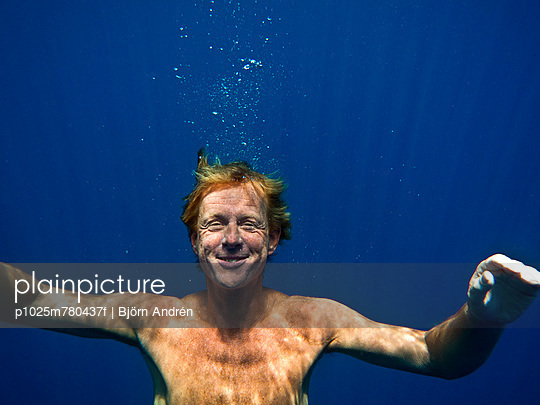 Portrait of a smiling shirtless man with arms out underwater - p1025m780437f by Björn Andrén