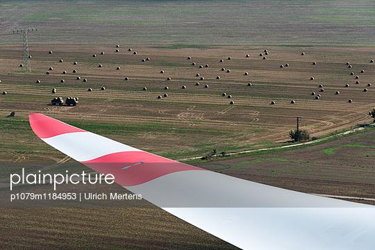 Windkraftflügel vor Landschaft mit Strohballen - p1079m1184953 von Ulrich Mertens