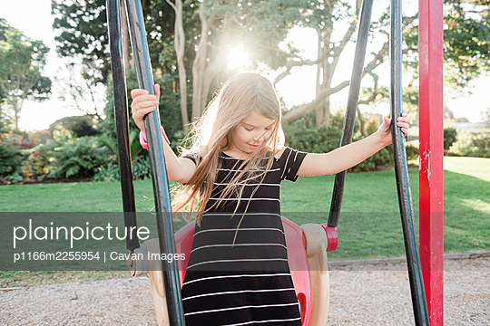 Young smiling girl standing on a swing at a public playground - p1166m2255954 by Cavan Images