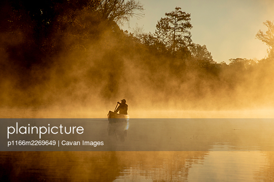 Sunrise canoe ride on foggy river. - p1166m2269649 by Cavan Images