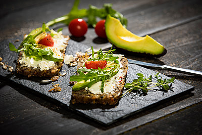 Onion bread with cream cheese, parma ham, avocado, rucola, thyme and tomato - p300m1587672 by Roman Märzinger