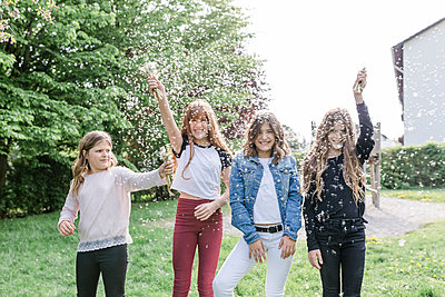 Four happy girls playing with dandelion seeds - p300m2156691 by Stefanie Baum