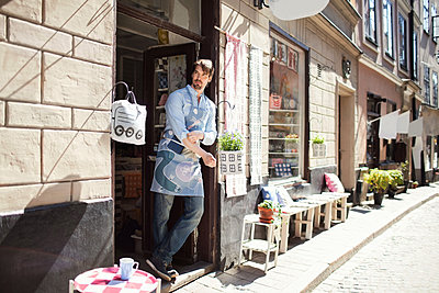 Confident man wearing apron standing at entrance of fabric shop - p426m1179368 by Maskot