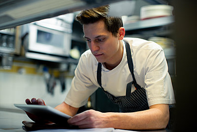 Chef wearing blue apron standing in kitchen, using digital tablet. - p429m2202246 by Sofie Delauw