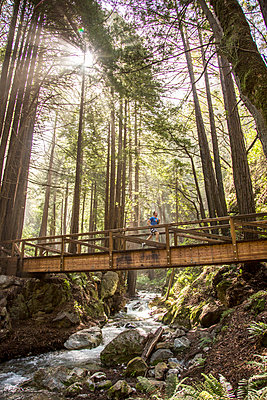 Caucasian man running on bridge over forest stream - p555m1482113 by Adam Hester