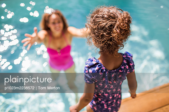 Daughter preparing to jump into arms of mother in sunny swimming pool - p1023m2238572 by Tom Merton