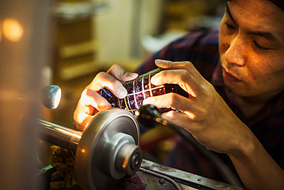 A craftsman at work at a machine, etching or scoring a coloured glass object.  - p1100m1185843 by Mint Images