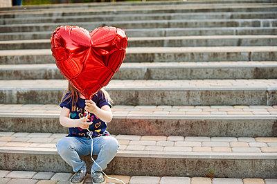 Girl hiding face behind a red balloon - p1412m1550499 by Svetlana Shemeleva
